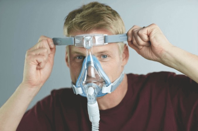 side sleeper putting on a cpap mask